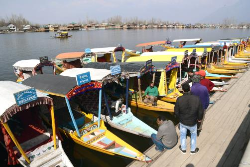 Boatmen waiting for customers banks of Dal lake in Srinagar on Monday.