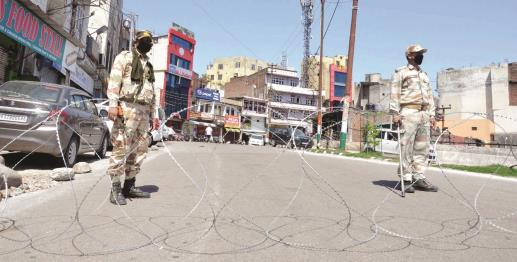 Security personnel stand guard on a closed road in Jammu on Wednesday. JL Baru
