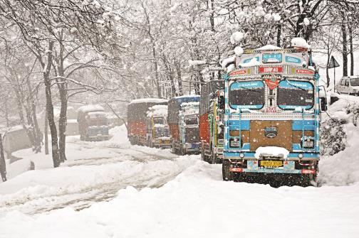 Trucks stranded at Srinagar-Jammu National highway during heavy snowfall, in Qazigund on Tuesday. ANI Photo