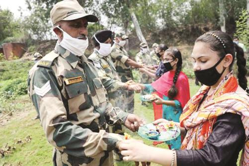 Young women tie rakhis on the wrists of Border Security Force (BSF)  personnel on the eve of Raksha Bandhan festival, at Inter National Border Octroi post in Suchetgarh, Jammu.