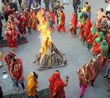 Girls in traditional attire dance around a bonfire as they celebrate Lohri festival in Jammu.