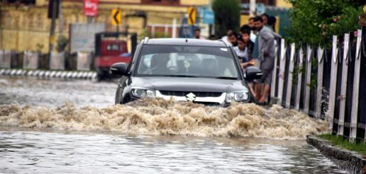 A vehicle struggles to move through the waterlogged road in Srinagar.