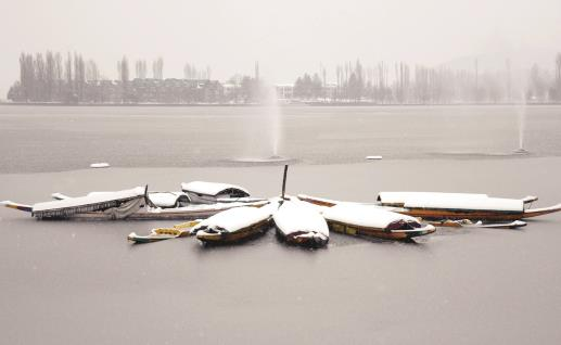 Snow covered shikaras moored on Dal Lake in Srinagar on Monday. ANI Photo