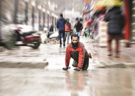 A handicapped man crosses a road during rains in Srinagar on Wednesday. Sheikh Faizan/JL