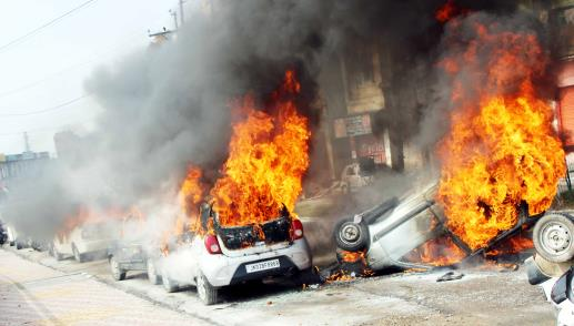 Vehicles stand in flames after it was set on fire by a mob