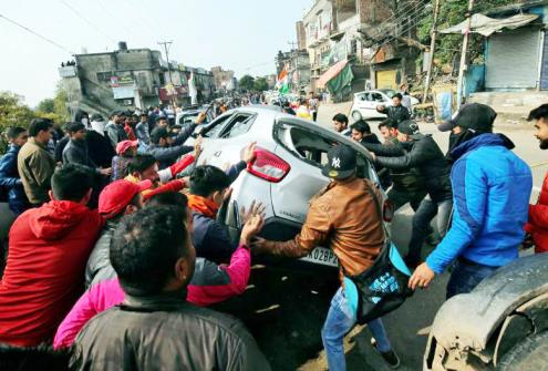 Demonstrators overturn a car during a protest.