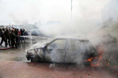 Firefighters douse flames on a vehicle set on fire by a mob during a protest in Jammu.