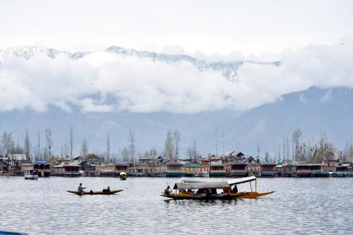 Shikaras cross Dal Lake with the backdrop of snow covered mountains in Srinagar.