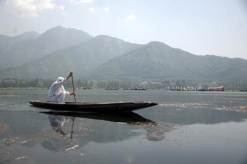 Woman paddling shikara on Dal Lake.