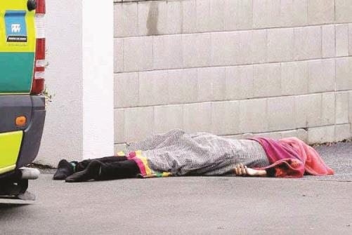A body lies on the footpath outside a mosque in central Christchurch, New Zealand.