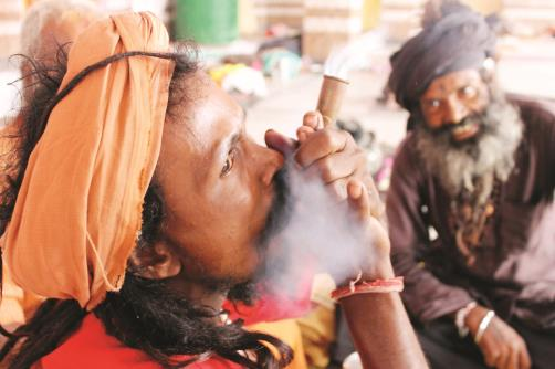 A Sadhu smokes a pipe at a base camp before registering for the annual  pilgrimage to the Amarnath cave shrine, in Jammu. (Baru/JL)