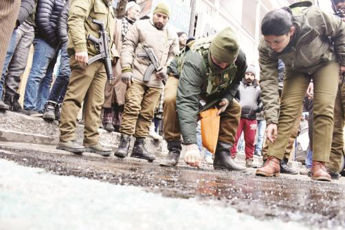 Security personnel inspect a spot after a grenade attack at Ghanta Ghar in Srinagar's Lal Chowk on Friday. Sheikh Faizan