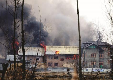 Flames and smoke billows from residential houses where militants hiding during a encounter south Kashmir Pulwama district, on Monday.