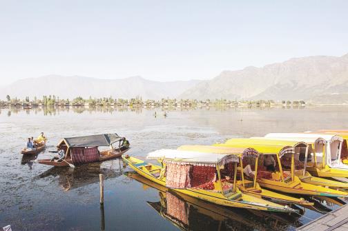 A boatman rides a boat on a deserted Dal Lake in Srinagar on Wednesday. (ANI Photo)