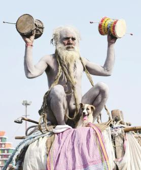 A Naga Sadhu with his dog sitting on camel offers prayer outside their temporary tent at bank of river Ganga during the ongoing Kumbh Mela-2019 on Sunday. (ANI)