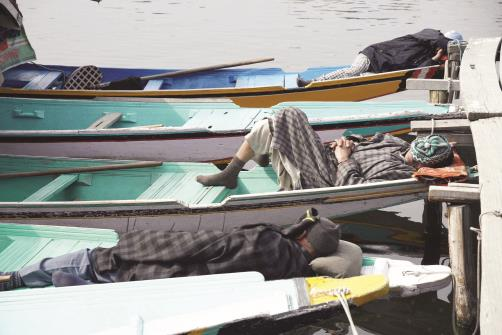 Boatmen take rest inside Shikaras as tourists visit has declined in the valley due to prevailing situation at Dal Lake in Srinagar on Monday. @ANI
