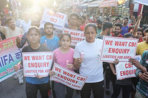 Children holding placards demanding CBI enquiry into Rassana Murder and Rape case during a canddle light march in Jammu.