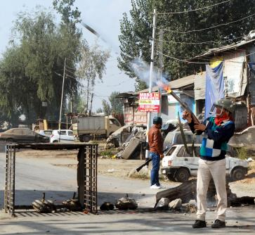 A policeman fires a teargas shell towards protesters during a protest in Srinagar.