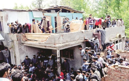 People gather at the broken house where Hizbul Mujahideen militants were killed in Panzgam area of Pulwama on Saturday. Sheikh Faizan/JL