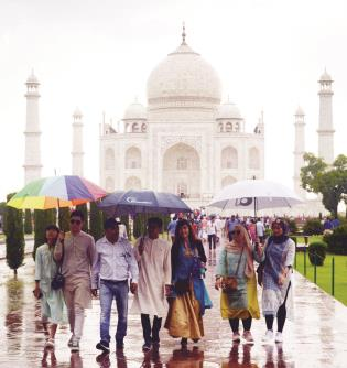 Tourists holding  umbrella during rain at  Taj Mahal in Agra on Monday. (ANI Photo)