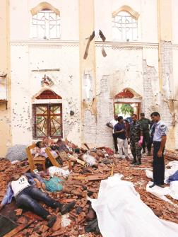 Security officials stand next to the dead bodies after a bomb blast inside a church in Negombo, Sri Lanka on Sunday. (REUTERS)