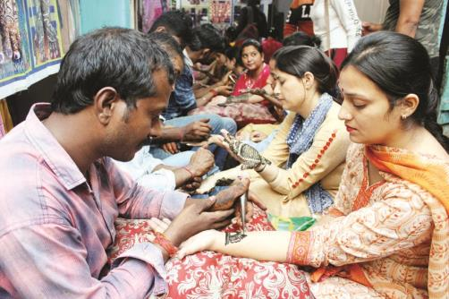 Women get their hands decorated with henna on the eve of 'Karva Chauth' festival in Jammu on Wednesday.(JL Baru)