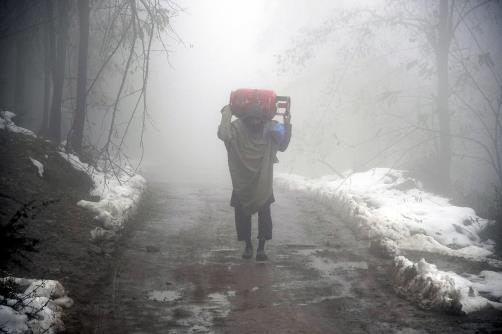 A man carries a gas cylinder on his shoulders during fog in Srinagar on Friday.