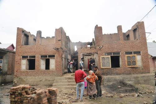 People gather at the damaged house where militants hiding after an encounter in which two Hizbul Mujahideen militants killed at Gopalpora area of  Kulgam district south Kashmir on Wednesday.