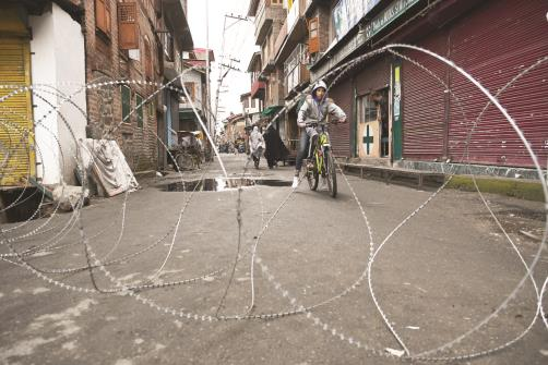 A boy riding a bicycle stops in front of razor wire during restriction imposed in old city Srinagar on Friday.(ANI Photo)