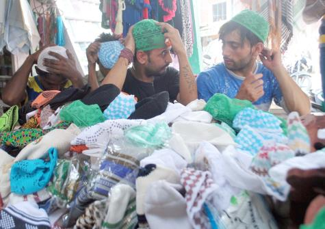 People selecting cap ahead of Eid-Ul-Fitr festival in Jammu on Sunday.