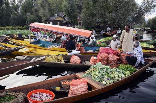 Vendors carry vegetables in their boats at the floating vegetable market on Dal Lake in Srinagar on Wednesday.