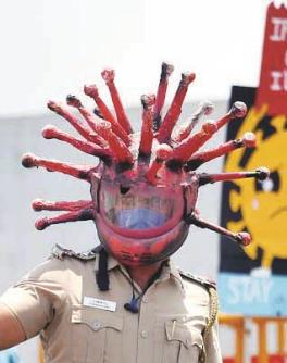 A police officer, wearing a helmet depicting coronavirus, requests a commuter to stay at home  during a nationwide lockdown to limit the spread of coronavirus, in Chennai.
