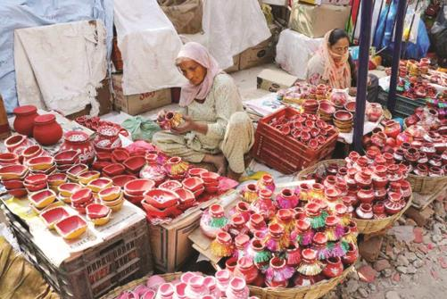 Vendors selling earthen pots wait for customers ahead of Karva Chauth festival, in Jammu on Sunday.